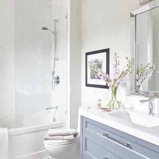 Inspiration för små moderna vitt badrum för barn, med möbel-liknande, grå skåp, ett hörnbadkar, en dusch/badkar-kombination, en toalettstol med separat cisternkåpa, vit kakel, keramikplattor, vita väggar, mosaikgolv, ett undermonterad handfat, bänkskiva i kvartsit, flerfärgat golv och med dusch som är öppen