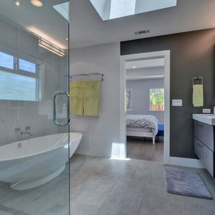 Inspiration for a mid-sized modern master porcelain tile and white tile laminate floor and gray floor bathroom remodel in San Francisco with flat-panel cabinets, dark wood cabinets, white walls, quartz countertops, a hinged shower door, a two-piece toilet and an integrated sink
