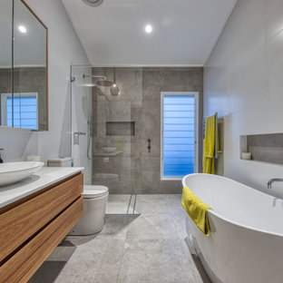 Large beach style master bathroom in Sydney with flat-panel cabinets, medium wood cabinets, a curbless shower, a one-piece toilet, gray tile, porcelain tile, porcelain floors, a vessel sink, grey floor, an open shower, white benchtops, a niche, a single vanity and a floating vanity.
