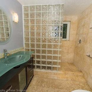 Esempio di una stanza da bagno padronale costiera di medie dimensioni con lavabo a consolle, consolle stile comò, ante in legno bruno, top in vetro, doccia aperta, WC a due pezzi, piastrelle beige, pareti multicolore e pavimento con piastrelle a mosaico