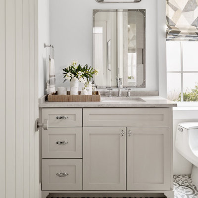Inspiration for a small coastal 3/4 white tile ceramic tile, gray floor and double-sink bathroom remodel in Houston with recessed-panel cabinets, white cabinets, a one-piece toilet, white walls, a drop-in sink, a hinged shower door, gray countertops and a built-in vanity