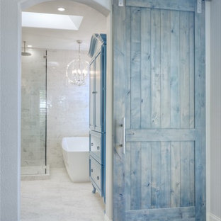 Photo of a large beach style master bathroom in San Diego with shaker cabinets, white cabinets, a freestanding tub, a double shower, gray tile, ceramic tile, grey walls, ceramic floors, an undermount sink, engineered quartz benchtops and a hinged shower door.