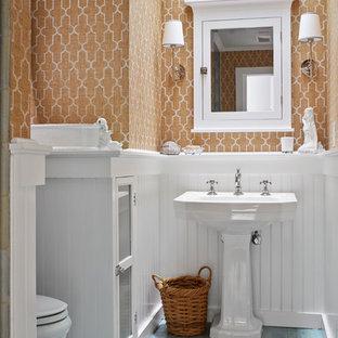 Maritimes Badezimmer mit Sockelwaschbecken, Duschnische, Wandtoilette mit Spülkasten, oranger Wandfarbe, gebeiztem Holzboden und türkisem Boden in New York