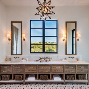 Photo of a mediterranean bathroom in Miami with furniture-like cabinets, dark wood cabinets, an open shower, white walls, an undermount sink, multi-coloured floor, cement tiles, solid surface benchtops and white benchtops.