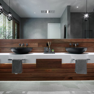 Photo of a large contemporary ensuite bathroom in Melbourne with a vessel sink, flat-panel cabinets, medium wood cabinets, grey tiles, porcelain tiles, grey walls, porcelain flooring, engineered stone worktops and grey floors.