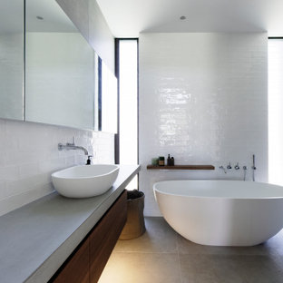 Inspiration for a mid-sized contemporary master bathroom in Central Coast with beaded inset cabinets, dark wood cabinets, a freestanding tub, an open shower, a wall-mount toilet, subway tile, white walls, porcelain floors, a console sink, concrete benchtops, grey floor, an open shower and grey benchtops.