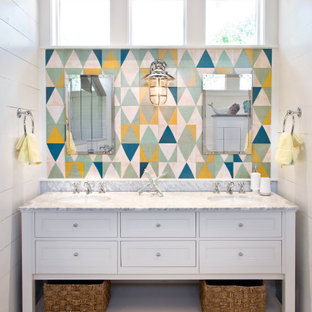 Photo of a mid-sized beach style kids bathroom in Austin with shaker cabinets, white cabinets, an alcove shower, multi-coloured tile, marble benchtops, a hinged shower door, white benchtops, a double vanity, a freestanding vanity, white walls, wood-look tile, an undermount sink, vaulted and planked wall panelling.