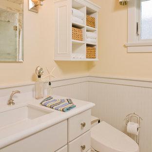 Modelo de cuarto de baño marinero con armarios con paneles con relieve, puertas de armario blancas, ducha esquinera, bidé, paredes amarillas, suelo de piedra caliza y encimera de acrílico