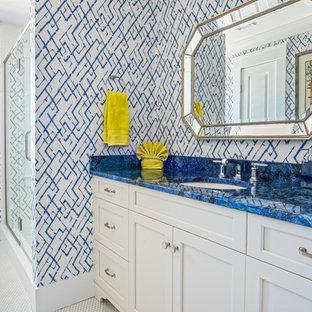 Modelo de cuarto de baño principal, clásico renovado, de tamaño medio, con armarios con paneles con relieve, puertas de armario blancas, bañera esquinera, ducha abierta, sanitario de una pieza, baldosas y/o azulejos azules, baldosas y/o azulejos blancos, baldosas y/o azulejos de vidrio, paredes azules, suelo con mosaicos de baldosas, lavabo encastrado, encimera de vidrio y encimeras azules