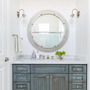 Imagen de cuarto de baño marinero con puertas de armario azules y suelo con mosaicos de baldosas