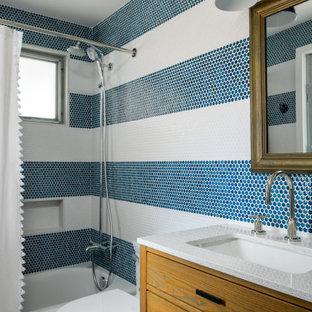 Maritim inredning av ett litet vit vitt badrum för barn, med släta luckor, skåp i mellenmörkt trä, ett badkar i en alkov, en dusch/badkar-kombination, en toalettstol med hel cisternkåpa, blå kakel, keramikplattor, blå väggar, klinkergolv i porslin, ett undermonterad handfat, bänkskiva i kvarts, grått golv och dusch med duschdraperi