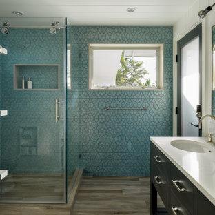 ハワイの中くらいのビーチスタイルのおしゃれな浴室 (フラットパネル扉のキャビネット、グレーのキャビネット、コーナー設置型シャワー、一体型トイレ、青いタイル、セラミックタイル、青い壁、磁器タイルの床、アンダーカウンター洗面器、クオーツストーンの洗面台、グレーの床、引戸のシャワー、白い洗面カウンター、洗面台1つ、独立型洗面台、塗装板張りの天井、パネル壁) の写真