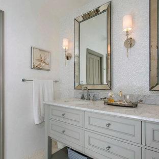 На фото: главная ванная комната среднего размера в стиле неоклассика (современная классика) с фасадами с утопленной филенкой, серыми фасадами, душем без бортиков, белой плиткой, плиткой из листового стекла, серыми стенами, полом из известняка, врезной раковиной, мраморной столешницей, бежевым полом и открытым душем с