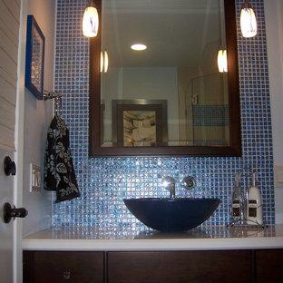 Diseño de cuarto de baño principal, minimalista, de tamaño medio, con armarios con paneles lisos, puertas de armario de madera en tonos medios, baldosas y/o azulejos azules, baldosas y/o azulejos de vidrio, paredes azules, lavabo sobreencimera y encimera de cuarzo compacto