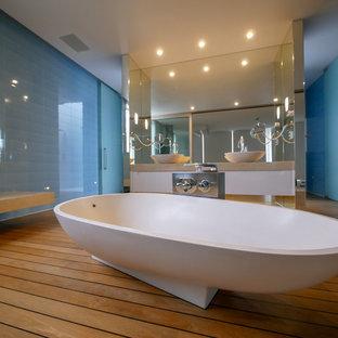 Ispirazione per una grande stanza da bagno contemporanea con consolle stile comò, ante bianche, vasca freestanding, WC sospeso, piastrelle blu, piastrelle diamantate, pareti blu, parquet chiaro, lavabo a bacinella, top in saponaria, pavimento marrone e top beige