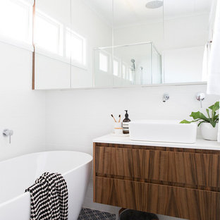 Inspiration for a beach style bathroom in Brisbane with flat-panel cabinets, dark wood cabinets, a freestanding tub, white walls, a vessel sink and grey floor.