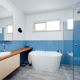 Inspiration for a large beach style master bathroom in Melbourne with flat-panel cabinets, light wood cabinets, wood benchtops, brown benchtops, a freestanding tub, a curbless shower, blue tile, white walls, a vessel sink and grey floor.