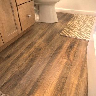 Ejemplo de cuarto de baño tradicional, de tamaño medio, con armarios con paneles empotrados, puertas de armario de madera oscura, combinación de ducha y bañera, sanitario de dos piezas, paredes beige, suelo vinílico, lavabo bajoencimera y encimera de acrílico