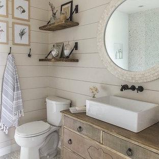 Ejemplo de cuarto de baño con ducha, marinero, pequeño, con armarios tipo mueble, puertas de armario con efecto envejecido, sanitario de dos piezas, paredes beige, suelo de baldosas tipo guijarro, lavabo sobreencimera, encimera de madera, suelo gris y encimeras marrones