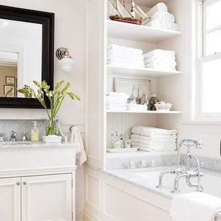 Mittelgroßes Maritimes Badezimmer En Suite mit Waschtischkonsole, verzierten Schränken, weißen Schränken, Marmor-Waschbecken/Waschtisch, Toilette mit Aufsatzspülkasten, weißen Fliesen, weißer Wandfarbe, Marmorboden und Unterbauwanne in New York