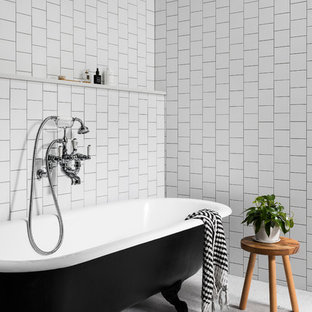 Photo of a mid-sized beach style master bathroom in Melbourne with white tile, white walls, ceramic floors, white floor and a claw-foot tub.