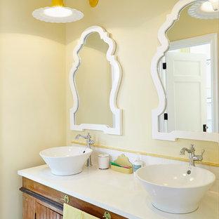 Foto de cuarto de baño marinero con lavabo sobreencimera, puertas de armario con efecto envejecido, baldosas y/o azulejos blancos y paredes amarillas