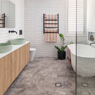Design ideas for a beach style wet room bathroom in Sydney with a freestanding tub, flat-panel cabinets, light wood cabinets, a wall-mount toilet, white tile, white walls, a vessel sink, grey floor, an open shower and white benchtops.