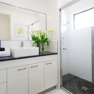 Inspiration for a beach style 3/4 bathroom in Other with flat-panel cabinets, beige cabinets, an alcove shower, white tile, white walls, a vessel sink, beige floor, a sliding shower screen and black benchtops.