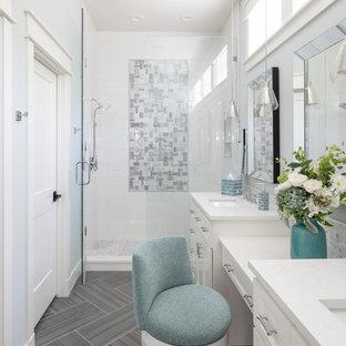 ダラスの大きいビーチスタイルのおしゃれなマスターバスルーム (白いキャビネット、グレーのタイル、マルチカラーのタイル、白いタイル、青い壁、アンダーカウンター洗面器、珪岩の洗面台、開き戸のシャワー、白い洗面カウンター、落し込みパネル扉のキャビネット、アルコーブ型シャワー、グレーの床) の写真