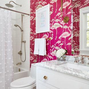 トロントのトランジショナルスタイルのおしゃれな子供用バスルーム (家具調キャビネット、白いキャビネット、アルコーブ型浴槽、シャワー付き浴槽、一体型トイレ、ピンクの壁、モザイクタイル、アンダーカウンター洗面器、珪岩の洗面台、白い床、シャワーカーテン、白いタイル、サブウェイタイル) の写真