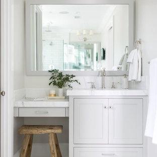 Diseño de cuarto de baño principal, tradicional renovado, de tamaño medio, con armarios estilo shaker, puertas de armario grises, sanitario de dos piezas, paredes grises, suelo de baldosas de porcelana, lavabo bajoencimera, encimera de esteatita y suelo blanco