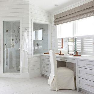 Modelo de cuarto de baño principal, costero, con puertas de armario grises, ducha esquinera, baldosas y/o azulejos grises, paredes blancas, suelo de madera pintada y armarios estilo shaker