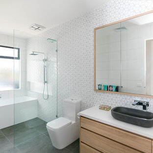 Large beach style master bathroom in Other with flat-panel cabinets, light wood cabinets, an alcove tub, a curbless shower, a one-piece toilet, white tile, white walls, a vessel sink, grey floor, an open shower, ceramic tile, porcelain floors, engineered quartz benchtops and white benchtops.