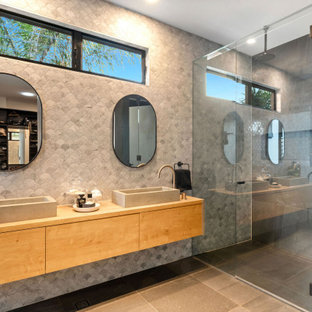 Contemporary bathroom in Sunshine Coast with flat-panel cabinets, medium wood cabinets, gray tile, a vessel sink, wood benchtops, grey floor, brown benchtops and a double vanity.