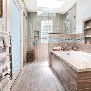 Cette image montre une grand salle de bain principale marine avec un placard à porte shaker, des portes de placard blanches, une baignoire encastrée, une douche à l'italienne, un carrelage marron, des carreaux de porcelaine, un mur bleu, un sol en carrelage de porcelaine, un lavabo encastré, un plan de toilette en terrazzo, un sol marron, une cabine de douche à porte battante et un plan de toilette blanc.