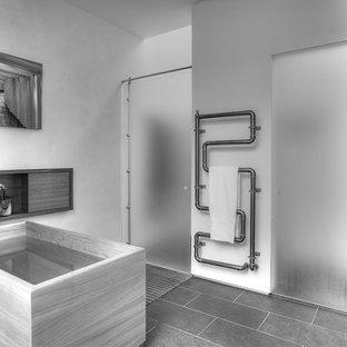 Foto de cuarto de baño principal, actual, de tamaño medio, con suelo negro, bañera exenta, ducha empotrada, ducha con puerta con bisagras, armarios con paneles lisos, sanitario de pared, suelo de pizarra, lavabo integrado y encimera de acrílico