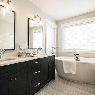 カルガリーの中サイズのトランジショナルスタイルのおしゃれなマスターバスルーム (シェーカースタイル扉のキャビネット、黒いキャビネット、置き型浴槽、ベージュの壁、ラミネートの床、アンダーカウンター洗面器、珪岩の洗面台、ベージュの床、白い洗面カウンター、アルコーブ型シャワー、ベージュのタイル、磁器タイル、開き戸のシャワー) の写真