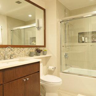 Idee per una piccola stanza da bagno contemporanea con lavabo sottopiano, consolle stile comò, ante in legno scuro, top in superficie solida, vasca ad alcova, doccia alcova, WC monopezzo, piastrelle beige, piastrelle di vetro, pareti beige, pavimento con piastrelle in ceramica, pavimento beige, porta doccia scorrevole e top bianco