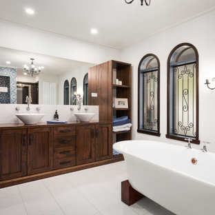 Inspiration for a mediterranean bathroom in Other with shaker cabinets, dark wood cabinets, a freestanding tub, white walls, a vessel sink, wood benchtops, white floor, brown benchtops, a double vanity and a built-in vanity.