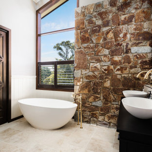 Design ideas for a mediterranean bathroom in Other with black cabinets, a freestanding tub, white tile, white walls, a vessel sink, beige floor, black benchtops, a double vanity, vaulted and decorative wall panelling.