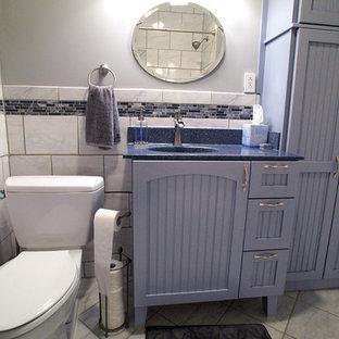 Cette image montre une petit salle de bain rustique avec un lavabo intégré, un placard avec porte à panneau encastré, des portes de placard grises, un plan de toilette en onyx, un carrelage noir et blanc et un sol en carrelage de céramique.