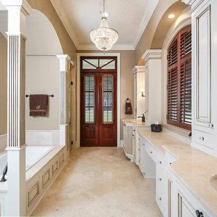 Источник вдохновения для домашнего уюта: большая главная ванная комната в классическом стиле с врезной раковиной, белыми фасадами, накладной ванной, бежевой плиткой, бежевыми стенами, фасадами с утопленной филенкой, мраморной столешницей, полом из травертина и плиткой из травертина