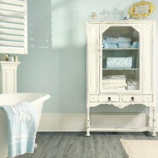 Ispirazione per una stanza da bagno padronale stile shabby di medie dimensioni con ante lisce, ante con finitura invecchiata, vasca con piedi a zampa di leone, pareti blu e parquet chiaro