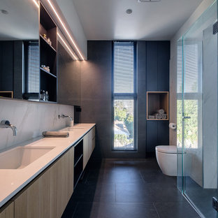 Inspiration for a mid-sized modern kids bathroom in Melbourne with flat-panel cabinets, light wood cabinets, an alcove shower, a one-piece toilet, white tile, porcelain tile, porcelain floors, a wall-mount sink, engineered quartz benchtops, grey floor, a hinged shower door, white benchtops and grey walls.