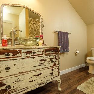 Modelo de cuarto de baño con ducha, de tamaño medio, con armarios tipo mueble, puertas de armario con efecto envejecido, sanitario de dos piezas, lavabo sobreencimera y encimera de madera