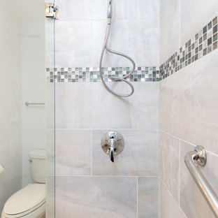 This is an example of a mid-sized transitional 3/4 bathroom in DC Metro with shaker cabinets, white cabinets, an alcove shower, a two-piece toilet, gray tile, white tile, porcelain tile, white walls, travertine floors, an undermount sink and quartzite benchtops.