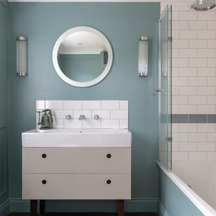 Inspiration for a contemporary bathroom in London with freestanding cabinets, grey cabinets, an alcove bath, a shower/bath combination, grey tiles, white tiles, metro tiles, blue walls, medium hardwood flooring, an integrated sink and white worktops.