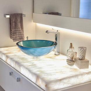 Idées déco pour une salle de bain moderne avec un placard à porte plane, des portes de placard blanches, un mur blanc, une vasque, un plan de toilette en onyx, un plan de toilette blanc et un sol en galet.