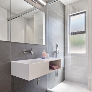 Bathroom - small contemporary kids' gray tile gray floor and single-sink bathroom idea in San Francisco with open cabinets, white cabinets, a wall-mount toilet, an integrated sink, white countertops and a floating vanity