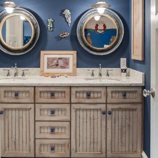 Inredning av ett klassiskt mellanstort badrum för barn, med ett undermonterad handfat, luckor med infälld panel, vit kakel, skåp i slitet trä, bänkskiva i kvarts, en toalettstol med separat cisternkåpa, keramikplattor, blå väggar och klinkergolv i keramik